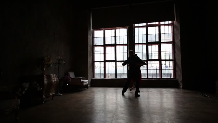 Silhouette of girl in red dress and man in black suit dancing tango