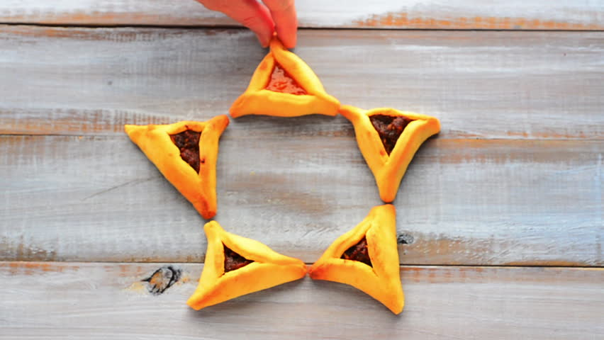 Woman hand creating a Star of David made out of Purim Cookies - Hamentashen (Ozen Haman) for Purim Jewish Holiday. Copy space