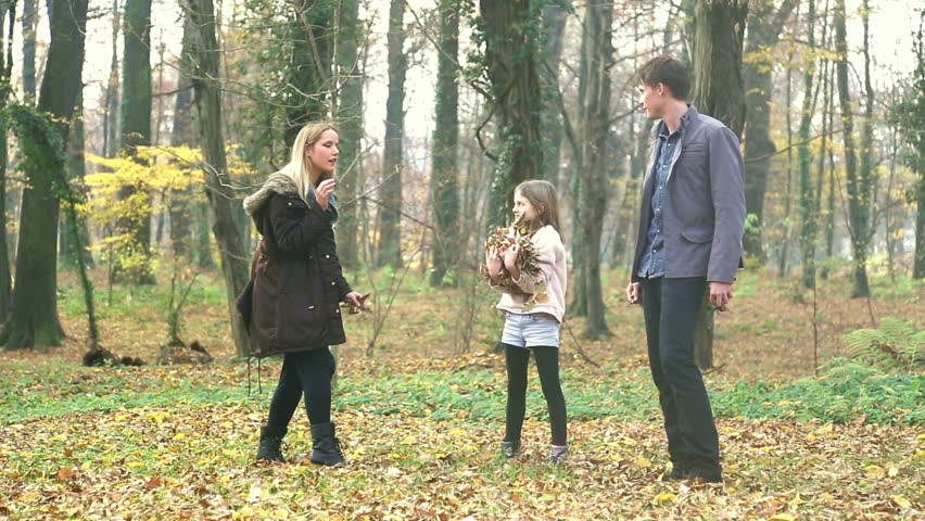 Beautiful young family having fun together, throwing leaves at each other in park, graded   Shutterstock HD Video #15442345