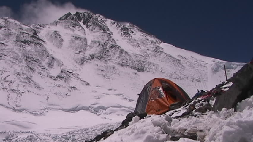 An expedition tent with Mt. Everest pinnacles and the summit in the background