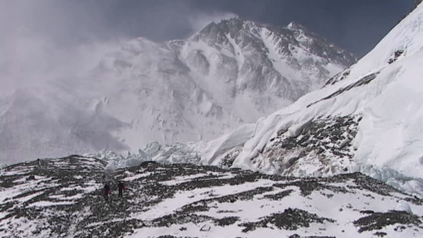 Climbers walking in the distance with Mt. Everest pinnacles and summit in the background