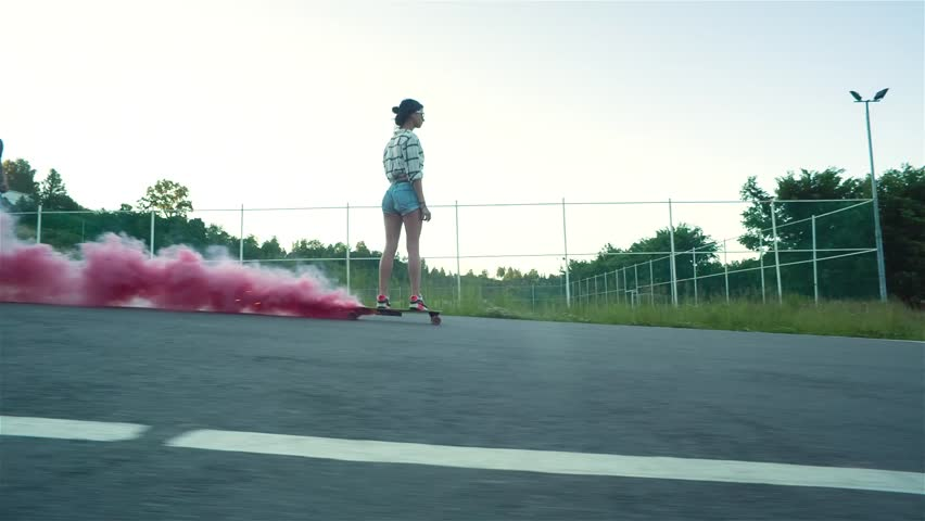Young style woman down the road on a skateboard with red smoke in sunny summer day | Shutterstock HD Video #15504484