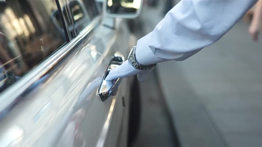 Close up shot of male hand in a glove opening door of a white luxury car