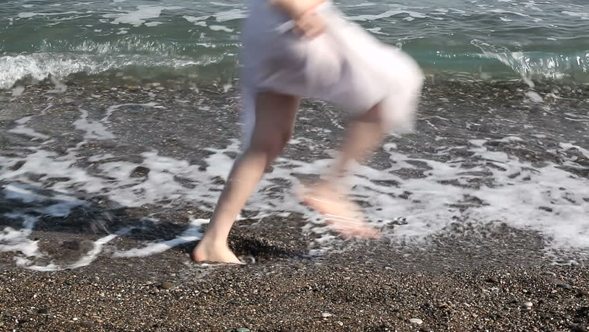 girl walking on the seaside, feet in the water close up #15510535