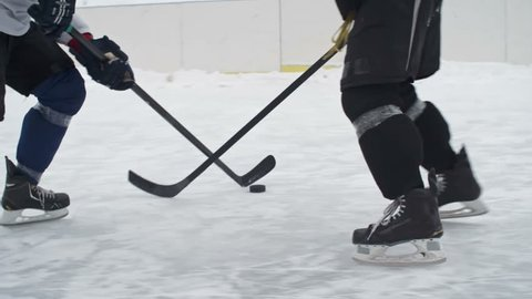 Tracking shot of a hockey forward carrying a puck while being pressured by an opposing defenseman and taking a slap shot being blocked by goalie