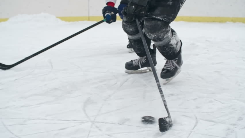 Low section close-up of hockey player being pressured by opponent while carrying a puck