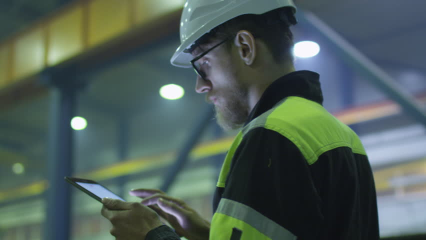 Engineer in hardhat is holding a tablet computer in a heavy industry factory. Shot on RED Cinema Camera.