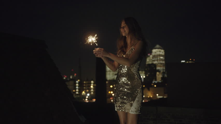Young adult woman dancing on rooftop with sparkler
