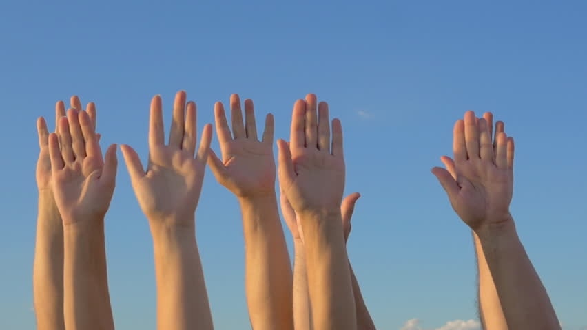 Slow motion of many hands raised against blue sky background.  Volunteering or voting concept
