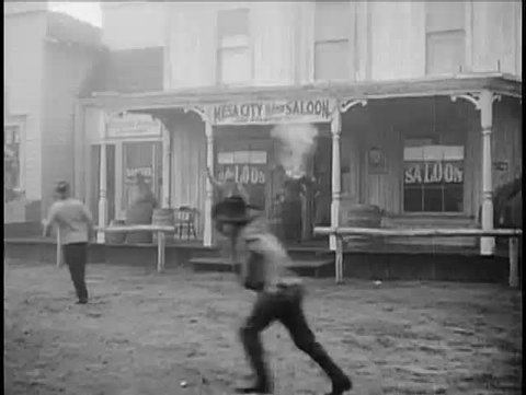 Wide shot of cowboys firing guns outside saloon, 1940s