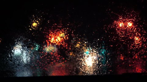 Slow Motion Rainy Dark Night view of the Wipers Motion From Inside a Car at a Red Traffic Light