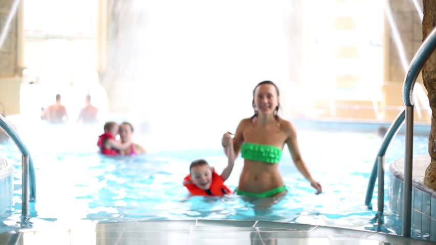 Woman and child in a rescue vest come out of pool holding hands | Shutterstock HD Video #15547015