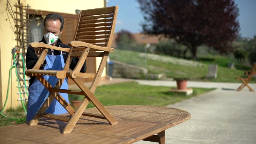 Handsome carpenter restoring a wooden chair with sandpaper. Garden furniture. Wide angle.