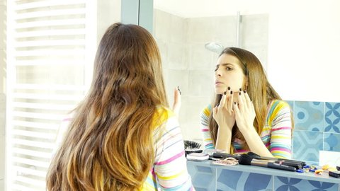 Woman in front of mirror driving crazy trying to cover pimple with makeup 4K.