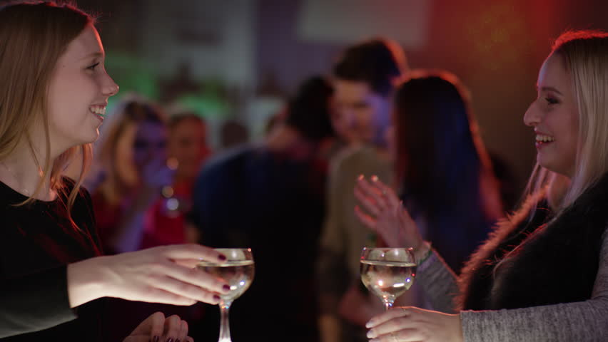 Two attractive girls at bar in club doing high five | Shutterstock HD Video #15565996