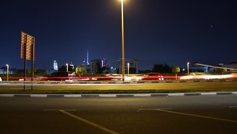DUBAI, UNITED ARAB EMIRATES - NOVEMBER 30, 2013: Night city road side view, time lapse. Cars sweep past, stop for a while, then rush again. Smooth ghosty vehicle traces, motion blur effect