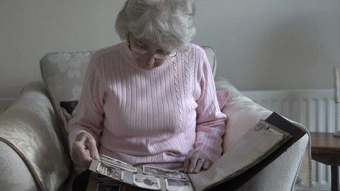 Senior woman looks at old photographs in album