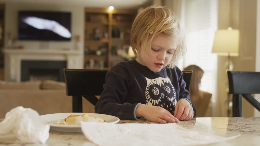 A little girl sitting at the kitchen counter at home playing with her food   Shutterstock HD Video #15611725