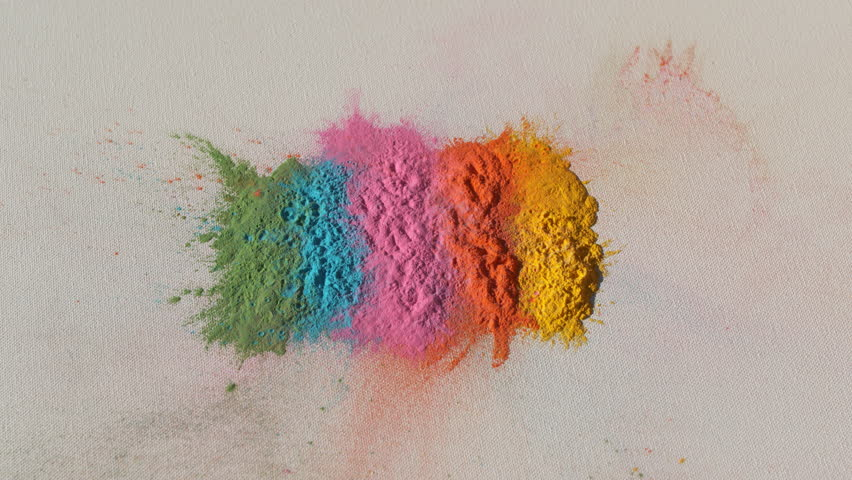 Colorful rainbow holi powder bounces off white canvas background into focus in rainbow shockwave pattern, slow motion