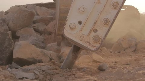 Hydraulic hammer breaker on excavator destroying rocks - Close up