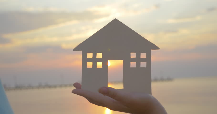 Close-up shot of woman holding home model and then family making house around it with hands. Sunset and sea as background. Zooming in to get the sun in the window
