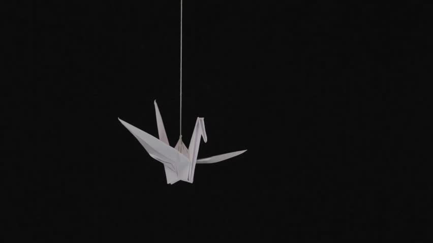 White Paper Origami Crane Swinging On Thread Against Black