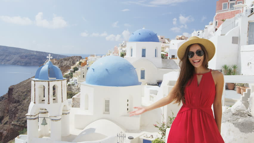 Woman with presenting showing welcome gesture in Oia Santorini, Greece, Europe. Young tourist is visiting famous landmark tourist destination wearing sunhat, sunglasses and red dress. SLOW MOTION. | Shutterstock HD Video #15646855