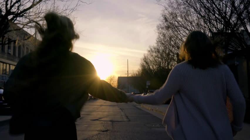 Carefree Teen Girls Hold Hands And Run Down City Street Toward Sunset (Away From Camera) | Shutterstock HD Video #15648385