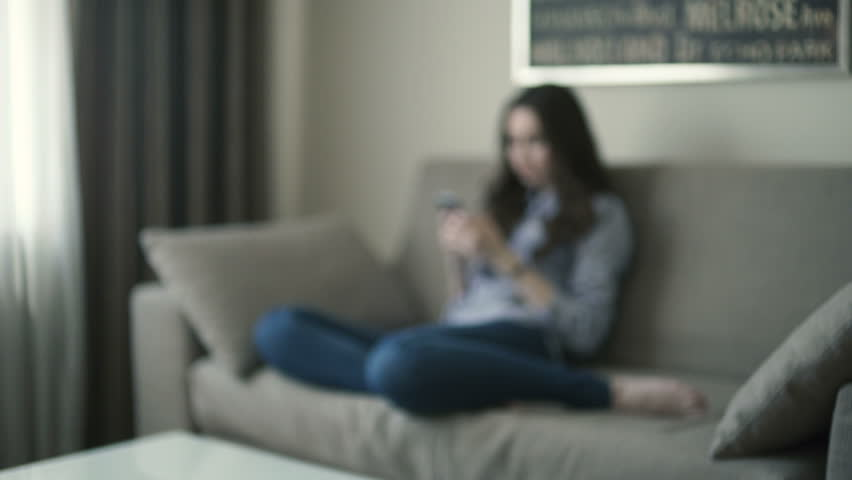 Beautiful woman sitting on the couch and using smartphone at home | Shutterstock HD Video #15661225