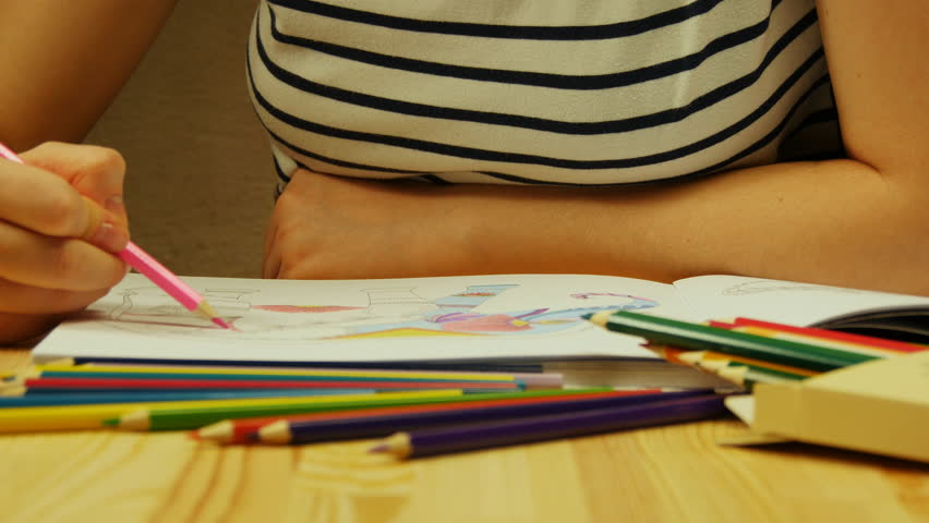 young woman holds a pencil and draws at home coloring for adults and children - Coloring Book Paper Stock