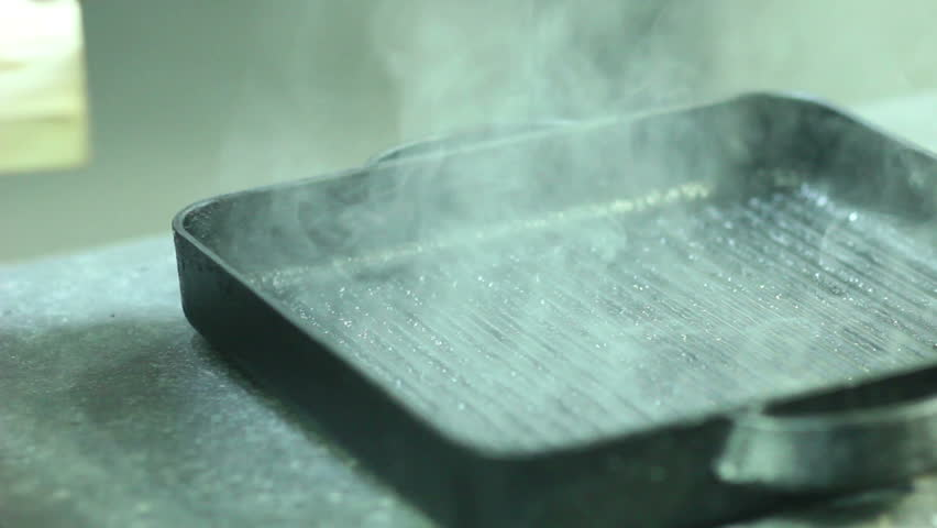 chef turning  steaks on grill pan