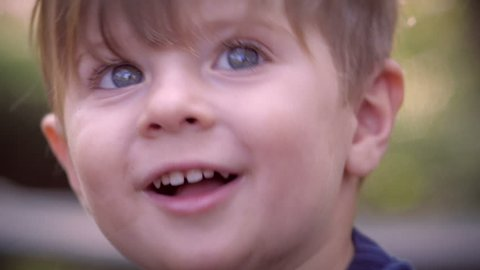 An intimate close up of a young little blond child looking and talking at the camera in slow motion. The child goes through a few different expressions including concern, happiness, worry, and joy.
