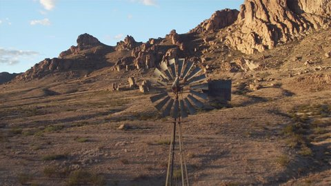 AERIAL: Flying over vintage windmill in sunny rocky mountain desert in the wild West