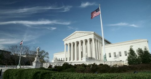 The US Supreme Court wide with flags and blue sky with light clouds. Also available in 4K SLog.