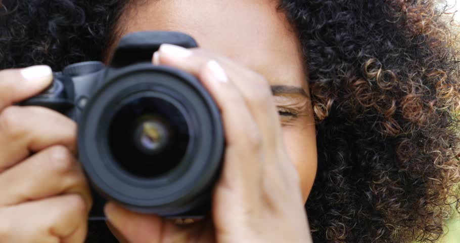 Young Afro Brazilian taking photos with a professional camera