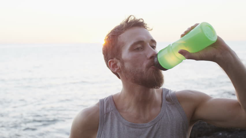 Fitness Man Drinking Water After Running Workout Outside On Beach Thirsty Male Athlete Having Cold