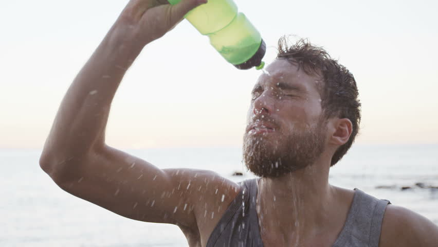Fitness man drinking water from bottle splashing water in face cooling down after running workout on beach. Thirsty athlete having cold refreshment drink sweating after intense exercise. SLOW MOTION. #15746395