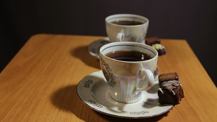 chocolate candies and tea set on a wooden table.cup of hot blak