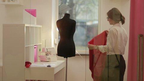 Fashion designer clothes maker draping dummy in studio.Fashion designer, tailor, dressmaker adjusting clothes on tailoring mannequin.