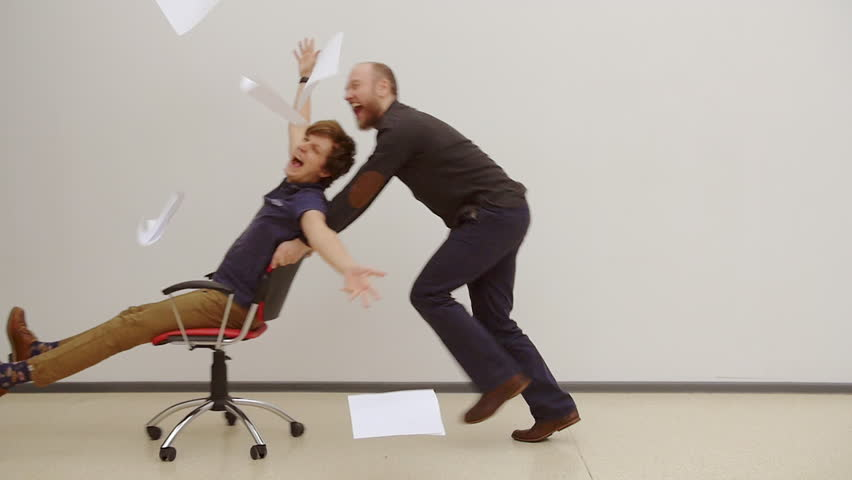Office chair race. Slow motion. Young guys have fun in the office during a break. Games of businessmen from large offices. Men celebrate a successful deal and throwing papers up. Office party.
