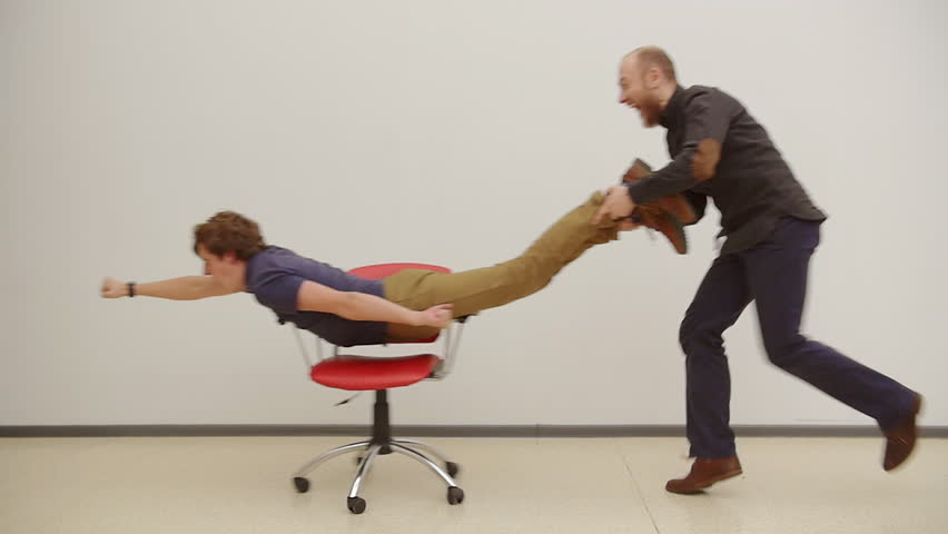 funny office chairs. young guys have fun in the office during a funny chairs f