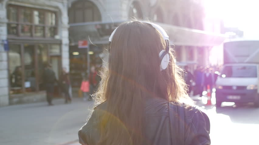 Girl with headphones walks in city