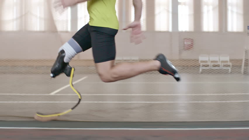 Tracking shot of Paralympic athlete with prosthetic leg running on track in slow motion