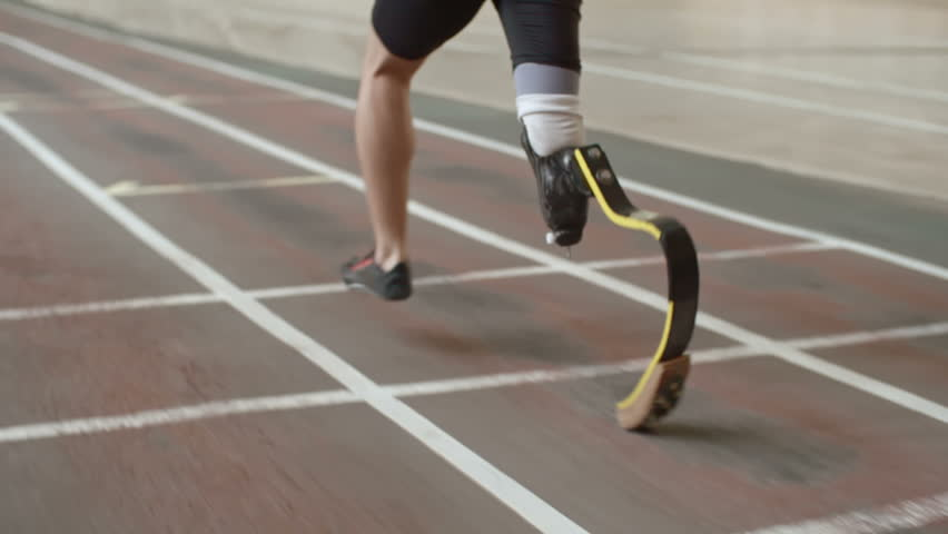 Follow shot of professional amputee athlete with artificial leg running on track in slow motion