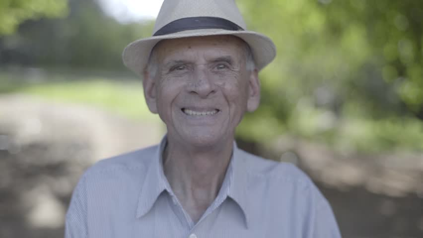 Outdoor portrait of smiling senior man in hat. Cinematic Video.