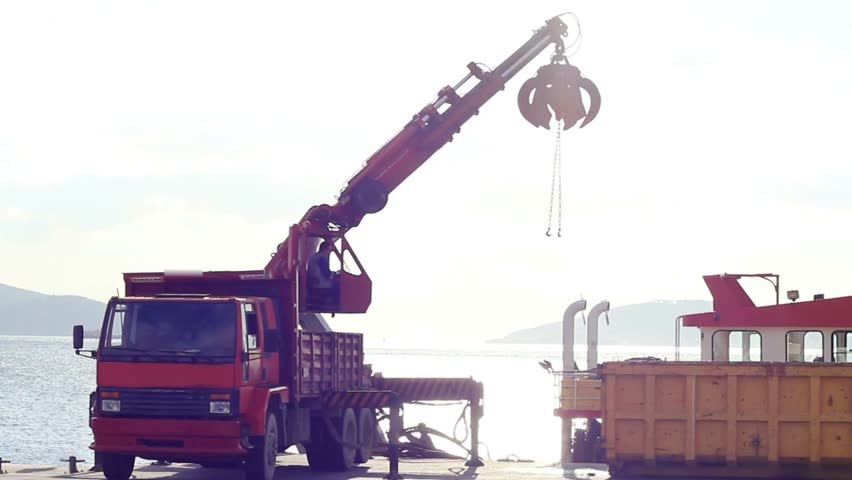 Port mobile crane lifting up the bucket. Bucket lifts up