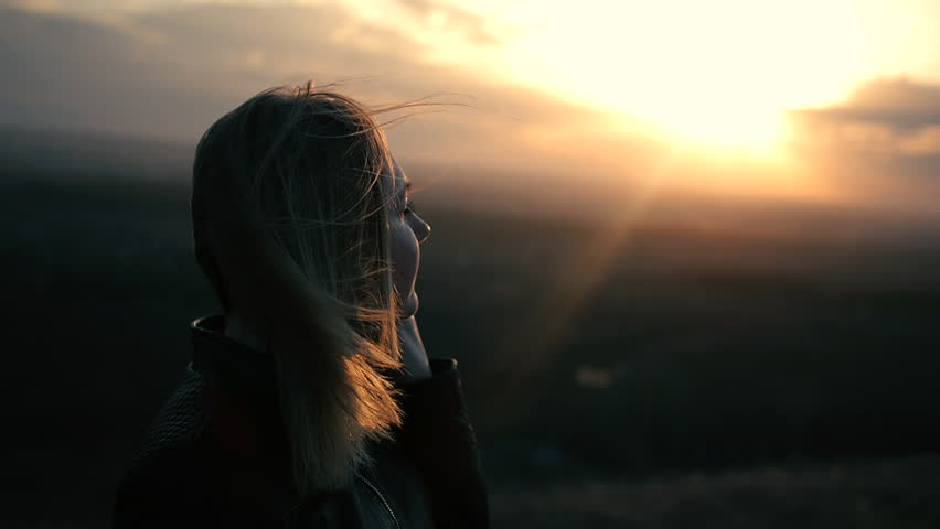beautiful girl watching the sunset smiling life dreaming of jumping the wind pulls the girl's hair silhouette backlight from the sun beautiful scenery red sunset sunset portrait of a beautiful woman