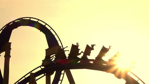 SLOW MOTION CLOSE UP: People riding extreme roller coaster attraction in amusement park at golden sunset. Rail looping coaster ride over the setting sun.