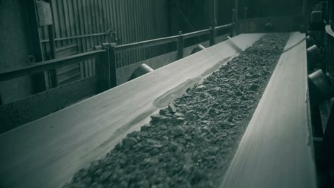 ore move on conveyor in modern processing plant. shoot with slider