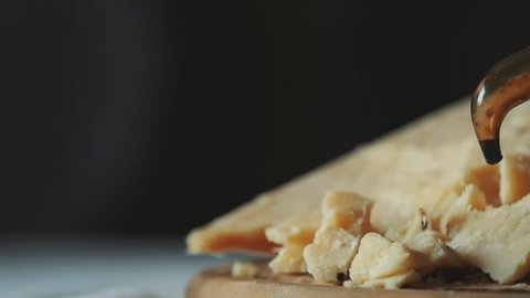 Modena balsamic vinegar poured on the famous hard cheese Parmigiano Reggiano in slowmotion.